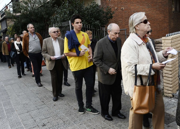 Image: People queue outside a polling station in Barcelona