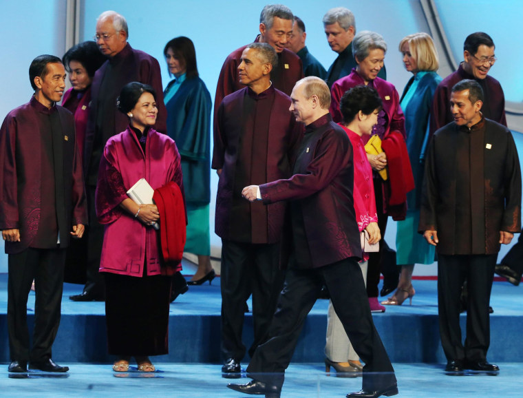 Russian President Vladimir Putin walks past President Barack Obama as the world leaders get into position for a family photo at the Water Cube or National Aquatic Center before a welcome banquet in Beijing, China, on Nov. 10.