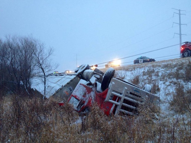 Image: A tractor-trailer hauling turkeys skidded off the highway in heavy snow, flipping onto its roof on Monday.