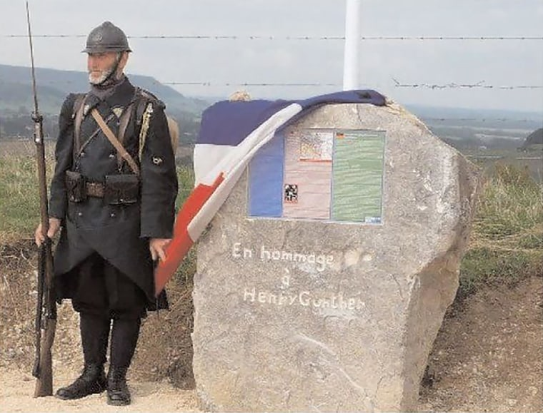 A man in WWI-era French uniform stands beside a memorial stone on the very spot where Henry Gunther fell on Nov. 11, 1918. The stone was unveiled by the French government as part of a 90th anniversary event in 2008.