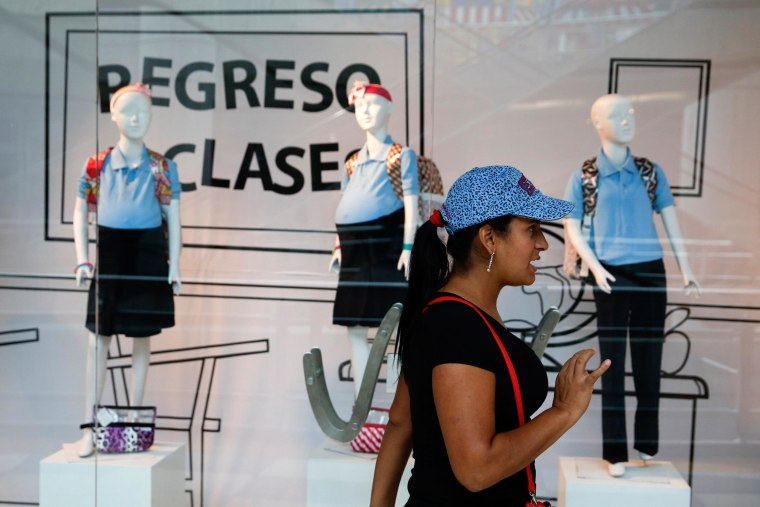 A woman reacts in front of a display showing mannequins of pregnant schoolgirls at a shopping mall in Caracas on Nov. 12.