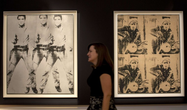 """Image: A woman walks between """"Triple Elvis"""" and  """"Four Marlons"""" by Warhol during media preview at Christie's auction house in New York"""