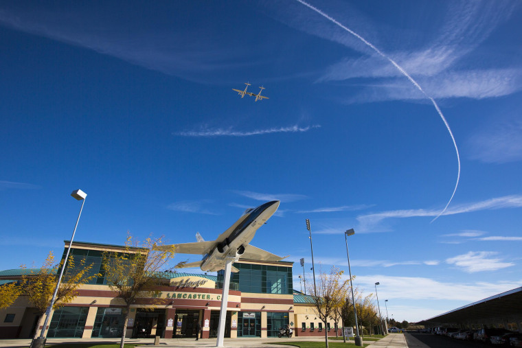 Virgin Galactic's WhiteKnightTwo mothership flies over Lancaster Municipal Stadium at the end of the memorial service for Scaled Composites test pilot Michael Alsbury, who died on Oct. 31 when the SpaceShipTwo rocket plane broke up during a test flight.