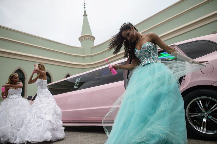 Image: Girls from the Cerro-Cora favela who turn 15 this year arrive in a pink limousine in Rio de Janeiro