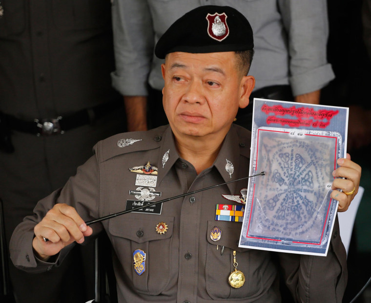 Image: Thai police officer shows a picture of a tattooed human skin