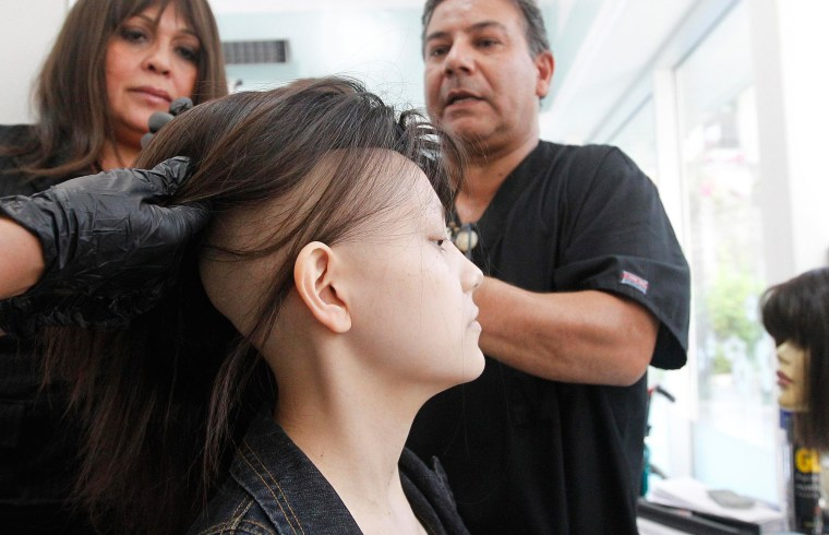 Image: Hair stylist Marcelo Avatte prepares to fit Isidora Serrano, a 14-year-old who lost her hair due to chemotherapy to treat her bone cancer, with a natural hair wig in the cancer ward of the Luis Calvo Mackenna Hospital in Santiago