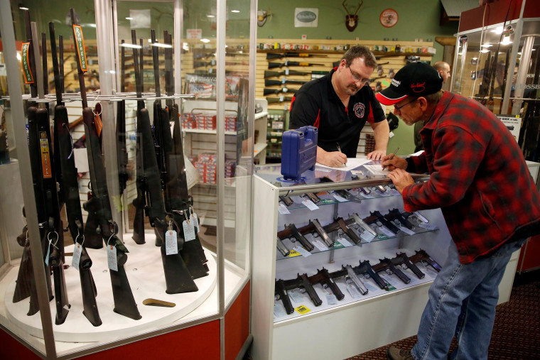 Image:  Steven King, left, fills out paperwork at Metro Shooting Supplies in Bridgeton, Mo.e