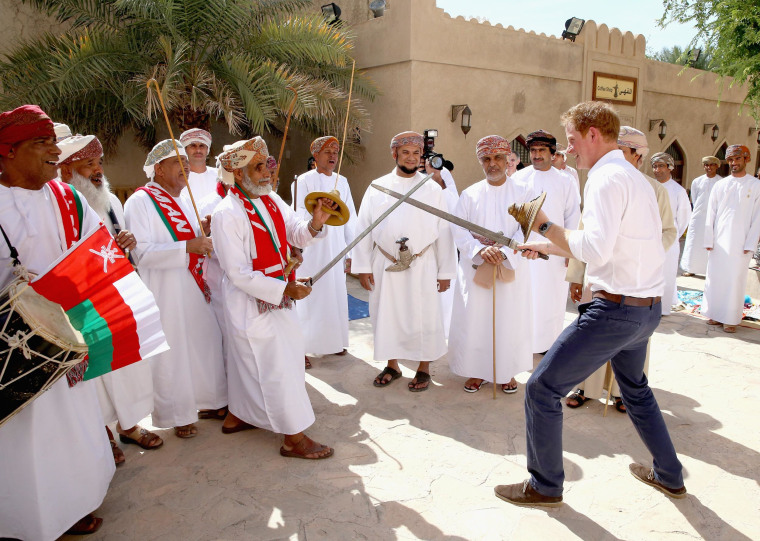 Prince Harry takes part in a mock sword fight as he meets traditional dancers during a visit to Nizra Fort on November 19, 2014 in Muscat, Oman.