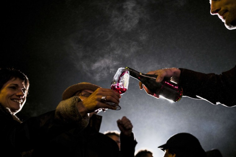 """Image: People celebrate the traditional event of """"the Sarmentelles"""" that starts the """"Beaujolais Nouveau"""" edition"""