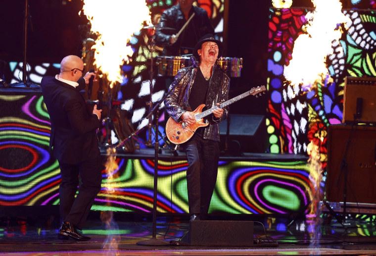 "Image: Carlos Santana performs ""Oye Como Va"" with Pitbull at the 15th Annual Latin Grammy Awards in Las Vegas"