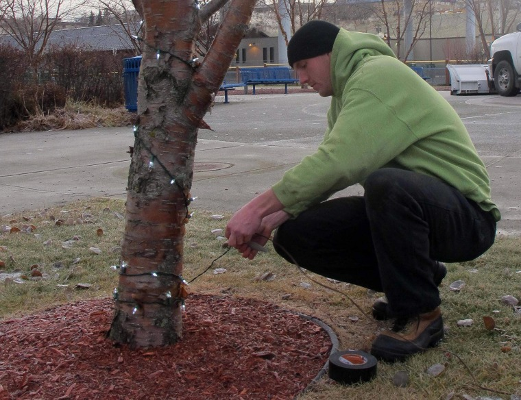 Image: Chantz Gaither hangs holiday lights in downtown Anchorage