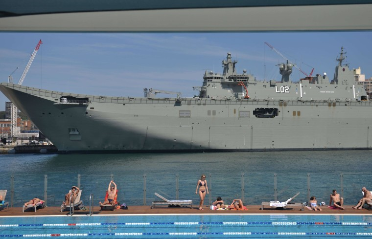 Sunbathers relax beside a swimming pool in Sydney in front of HMAS Canberra, which is berthed at the city's Garden Island naval base.