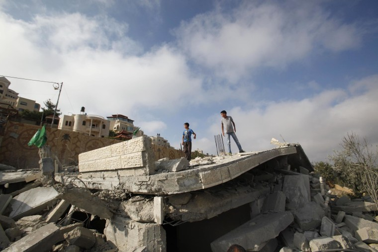 Palestinians stand on the remnants of the house of Hussam Kawasma, one of three Palestinians identified by Israel as suspects in the killing of three Israeli teenagers, after it was demolished by the Israeli army in the West Bank city of Hebron, on Aug. 18.