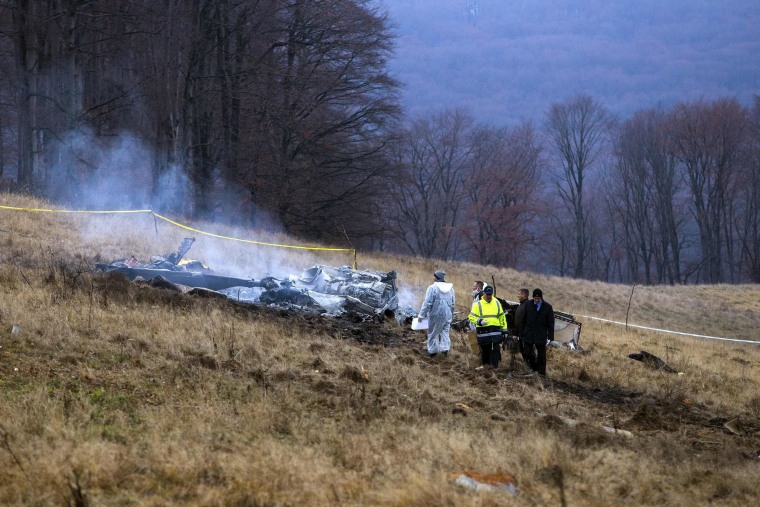 Image: Policemen and investigators are seen at the site where a military helicopter IAR-330 Puma built in Romania, crashed near Malancrav