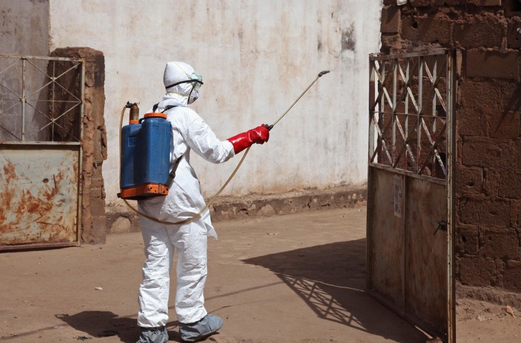 A health worker sprays disinfectant near a mosque after the body of a man suspected of dying from the Ebola virus was washed inside in Bamako, Mali, on Nov. 14.