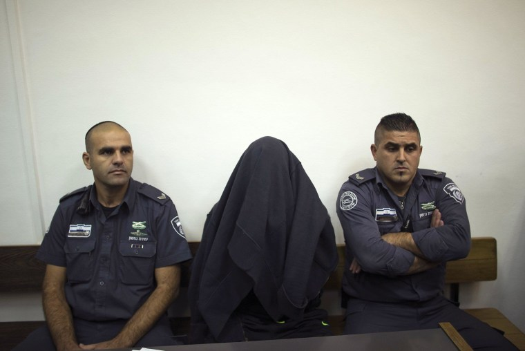 Image: Israeli prison guards sit beside a paramilitary border policeman at Jerusalem District court