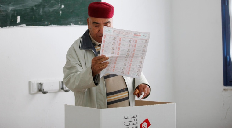 A man looks at his ballot while voting at a polling station during Tunisia's presidential election in Tunis on Nov. 23, 2014. Tunisians went to the polls on Sunday to vote for their first directly elected president since the 2011 revolution that ended the regime of Zine el-Abidine Ben Ali. REUTERS/Zoubeir Souissi