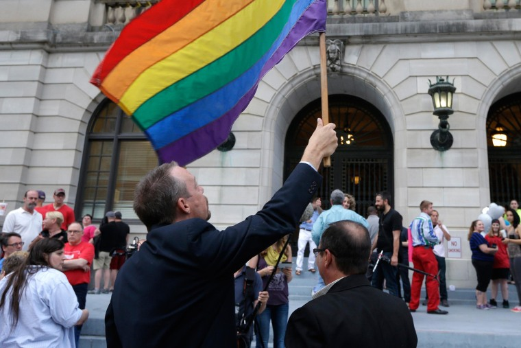 Image: Same-sex marriage supporters hold a flag at the Pulaski County Courthouse in Little Rock, Ark.