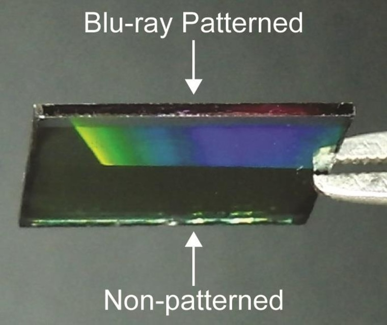 A surface partly covered by the Blu-ray pattern that shows how it diffuses light (as shown by the rainbow gradient).