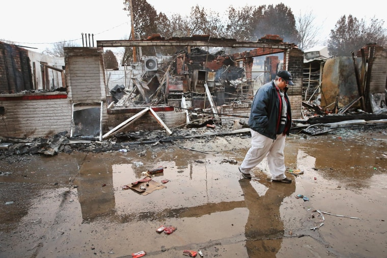 Image: Property manager Terri Willits looks over a gas station she manages that was set on fire when rioting erupted