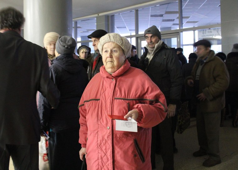 Tamara waits in line to receive a food donation at a former circus in the city of Donetsk