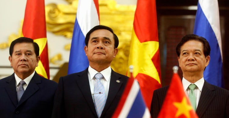 Thailand's Prime Minister Prayuth Chan-ocha (C) stands between Deputy Prime Minister and Foreign Minister, General Tanasak Patimapragorn (L) and his Vietnamese counterpart Nguyen Tan Dung (R) during a signing ceremony at the Government Office in Hanoi November 27, 2014. Prayuth is in Hanoi on a two-day visit to Vietnam on November 27 to November 28.