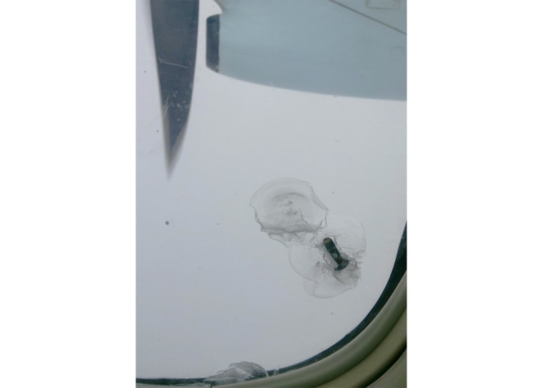 A bolt from the propeller of a commercial aircraft came loose and was lodged into a window of the fuselage.
