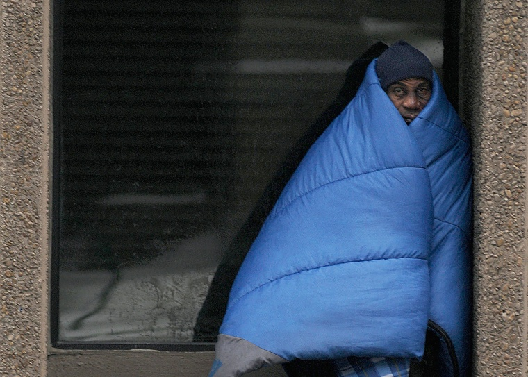 Homeless man tries to stay warm along an icy Peachtree Street after a snow carpeted the Deep South in Atlanta..