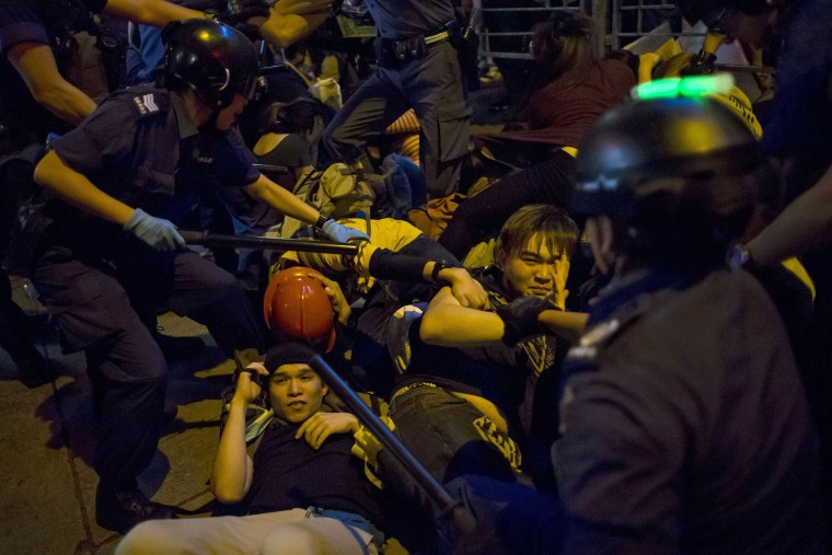 Image: Pro-democracy protesters fall on the ground as they are chased by riot police at Mong Kok shopping district in Hong Kong