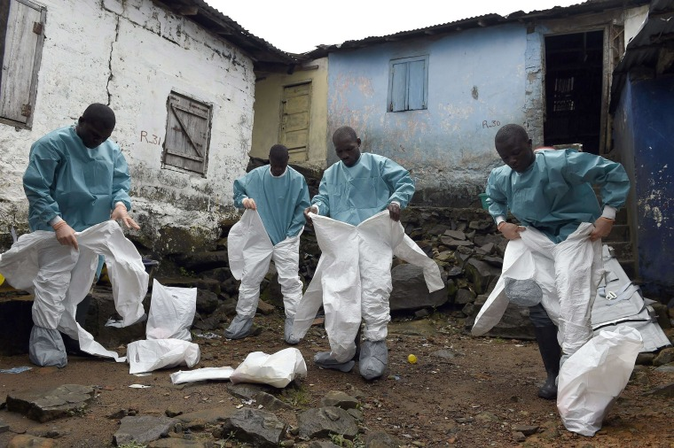 Medical staff members of the Croix Rouge NGO put on protective suits before collecting the corpse of a victim of Ebola, in Monrovia, on Sept. 29.
