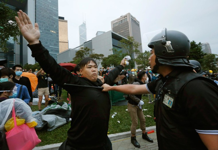 A pro-democracy protester blocks a riot policeman during a clash outside the government headquarters in Hong Kong December 1, 2014. Hong Kong police baton-charged and pepper-sprayed thousands of pro-democracy demonstrators in the early hours of Monday who were trying to encircle government headquarters, defying orders to retreat after more than two months of protests.