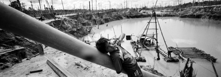 Image: A boy leans against a tube that is part of a rustic type of hydraulic jet known locally as a 'chupadera,' at a makeshift mining camp on May 28