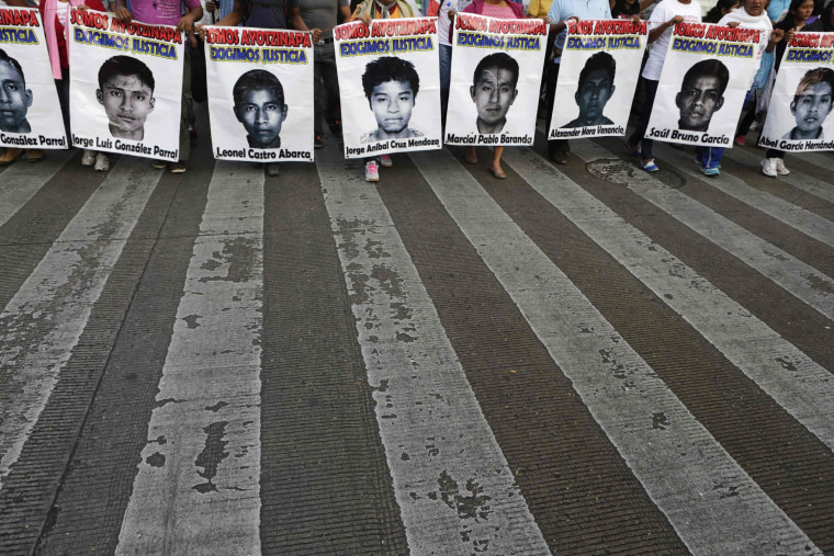 Image: Demonstrators carry photographs of the missing 43 trainee teachers during a protest in support of the students in Mexico City