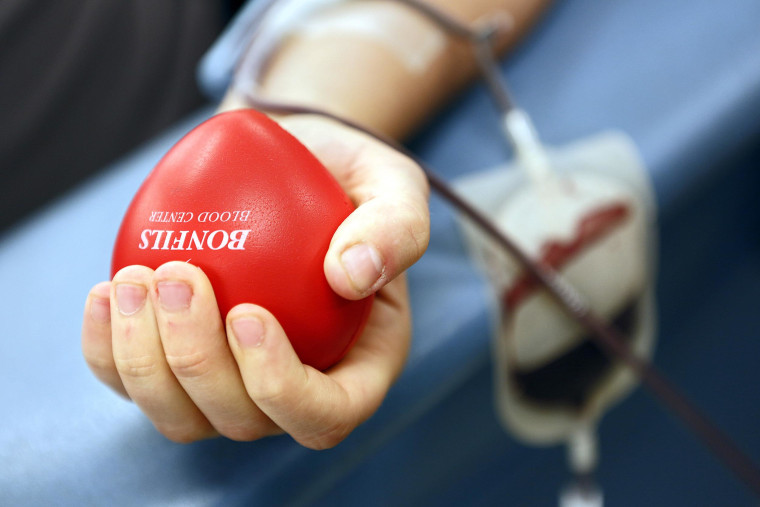 Image: Laura Jackson, 27, of Denver, Colo. squeezes a heart as she donates blood