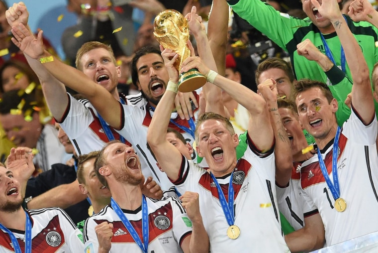 Image: Bastian Schweinsteiger of Germany and his teammates celebrate with the World Cup trophy