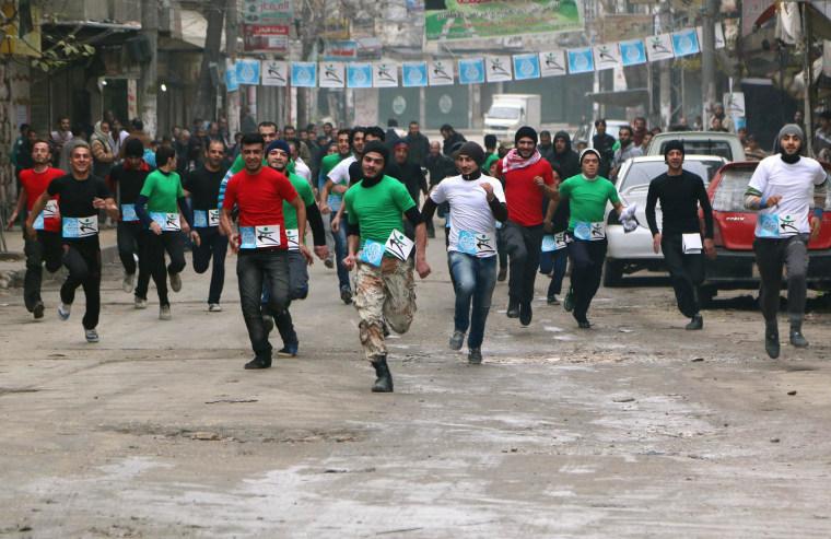 Image: Participants compete in a running race along a street in Aleppo's Bustan al-Qasr neighbourhood