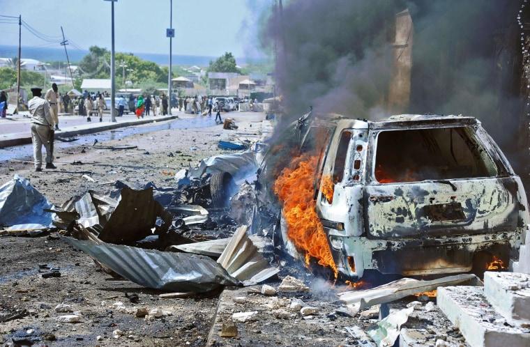 Image: A car burns following a blast in Mogadishu