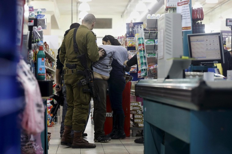 Image: Israeli police forces detain a suspected Palestinian at a supermarket, where another Palestinian stabbed two people according to police and an ambulance service, near an Israeli settlement in the occupied West Bank