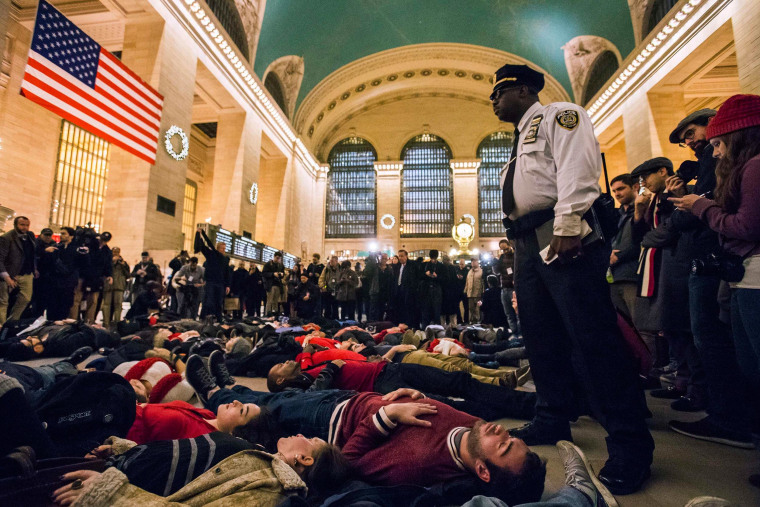 Image: A police officer stands over activists, demanding justice for the death of Eric Garner, as they stage a 'die-in' during rush hour at Grand Central Terminal in the Manhattan borough of New York