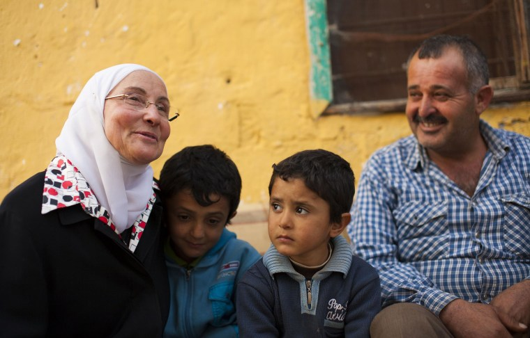 Image: Hazar Mahayni speaks with the father of young Waseem , a student at her school for Syrian refugees who had been missing classes to help his dad at work