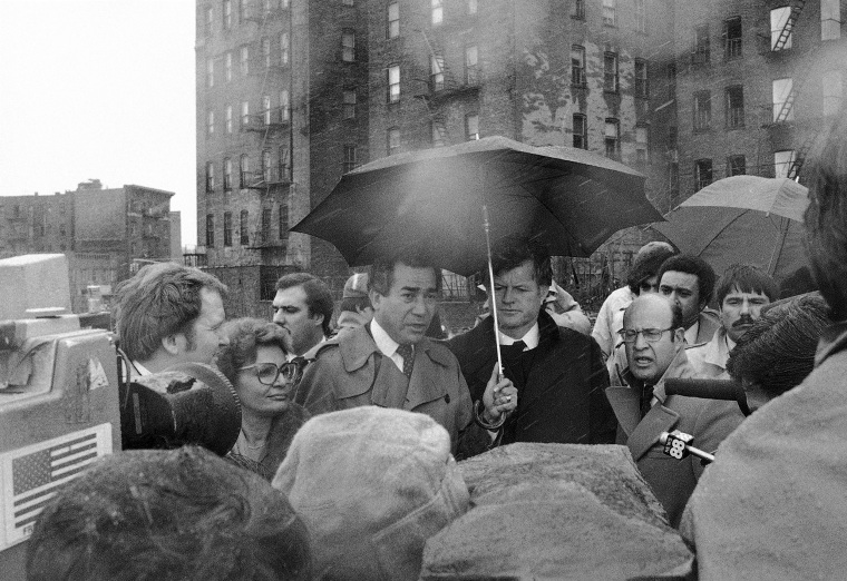 "Herman Badillo, center left, stands in cold, driving rain with Sen. Edward Kennedy on March 22, 1980 at the same place in the South Bronx where President Jimmy Carter stood three years ago and said ""Get me a map of the whole area and show me what should be done."" Kennedy said Carter had failed to deliver on his promises to the area."