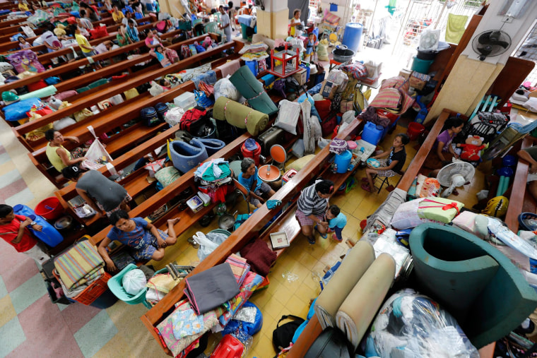 People shelter inside a church turned into a temporary evacuation center in Tacloban City, Philippines, on Dec. 5, 2014. Thousands of people were stranded after flights and sea travel were cancelled ahead of typhoon Hagupit's expected landfall.