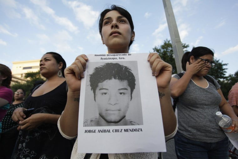 A woman holds a photograph of a missing student during a march in support of the Ayotzinapa Teacher Training College missing students, in Monterrey October 8, 2014.