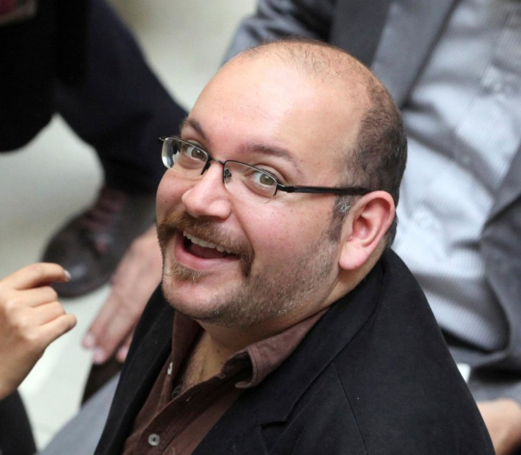 """Jason Rezaian, an Iranian-American correspondent for the Washington Post smiles as he attends a presidential campaign of President Hassan Rouhani in Tehran, Iran, April 11, 2013. The family of Rezaian jailed without charge in Iran is urging authorities in Tehran to release him, calling his incarceration a """"farce"""" 100 days after he was detained."""