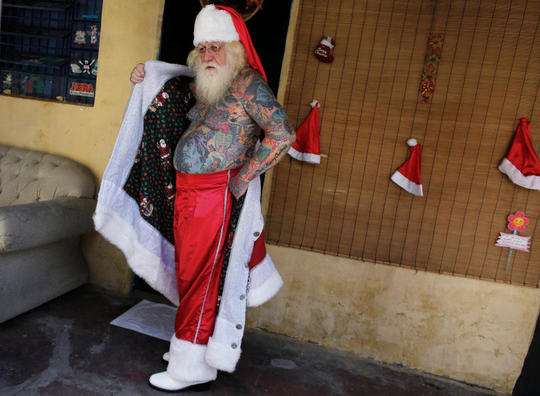 Image: Vitor Martins poses as he puts on his Santa outfit inside his house near Sao Paulo