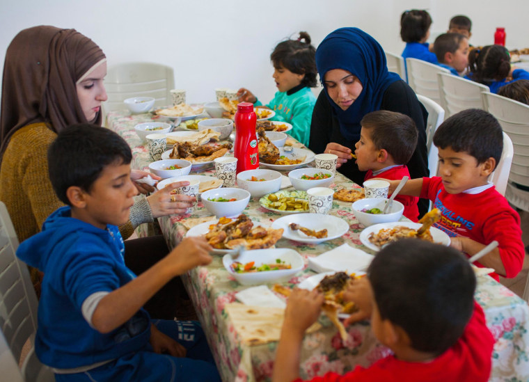 Siblings Obada, Amina, Hussein, Murad and Mustafa, sit at the lunch table with two staff members.