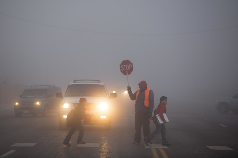 Image: Crossing-guard Felix Robles stops traffic as students cross the street during heavy fog