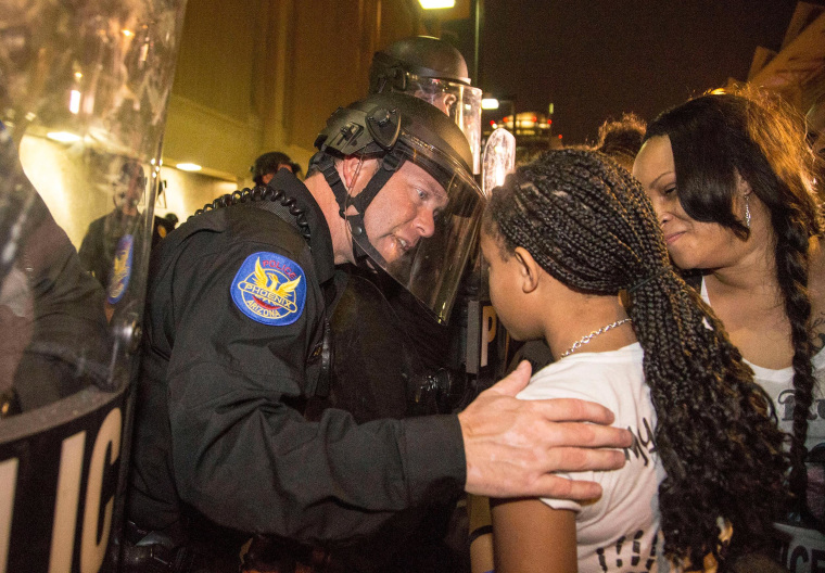 "A Phoenix police officer in riot gear talks with Aiyana Rains, 9, the daughter of Rumain Brisbon, as she marches with hundreds of protesters toward police headquarters in Phoenix on Dec. 8, 2014. Grasping her hand, the officer said, ""I'm sorry."""
