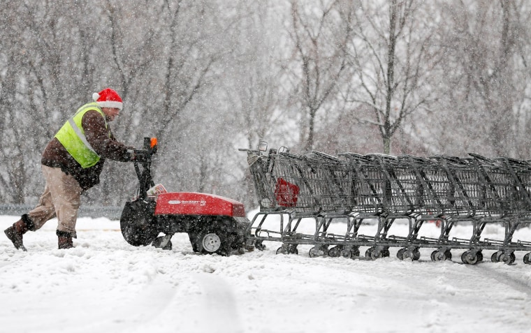 Image: A man pushes shopping carts through slushy snow at a supermarket in East Greenbush, New York.