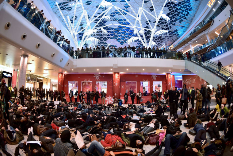 "Image: A group of protesters create a ""die-in"" at the Westfield shopping mall in West London"